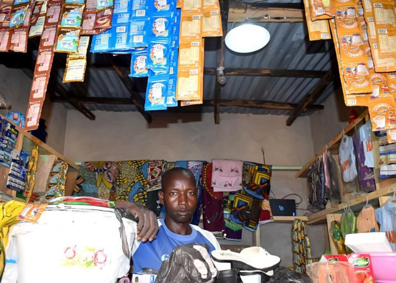 A merchant in Nigeria who uses a solar power kit for lighting and small electrical needs.